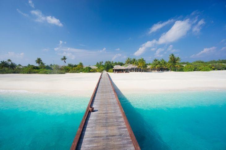 bird's eye view approaching tropical island resort from jetty