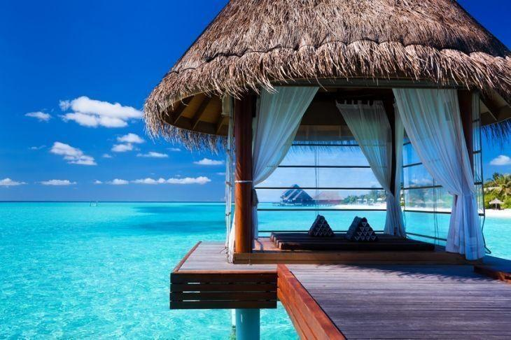Overwater spa and bungalows in tropical blue lagoon