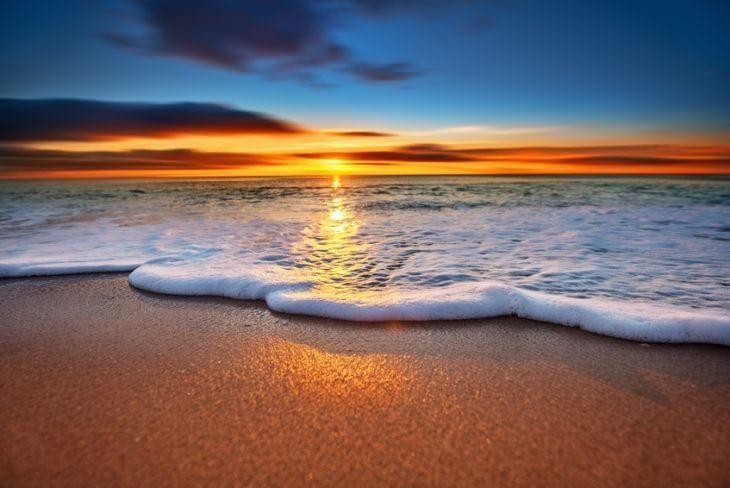 Sunrise light shining on ocean waves.