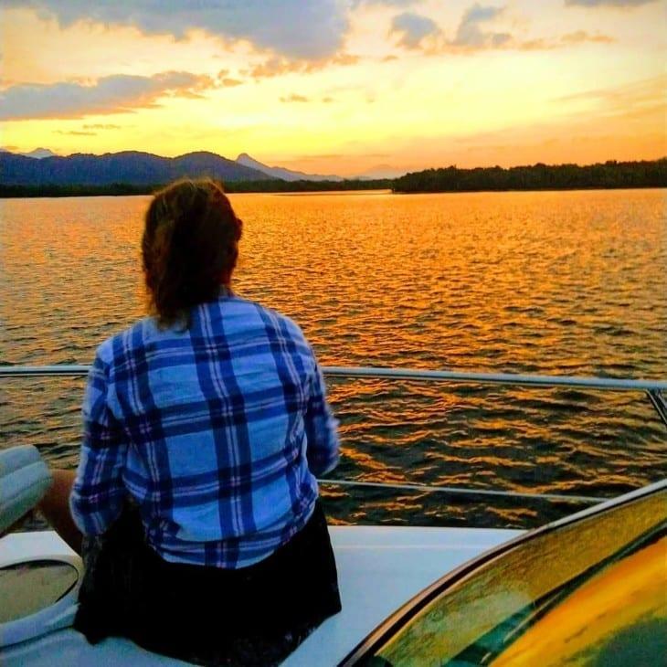 Mulher observa o pôr do sol